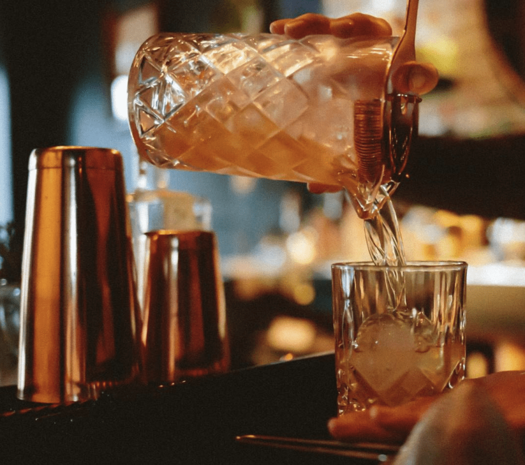 Tío Navaja bar area pouring a cocktail into glass romantic panamá