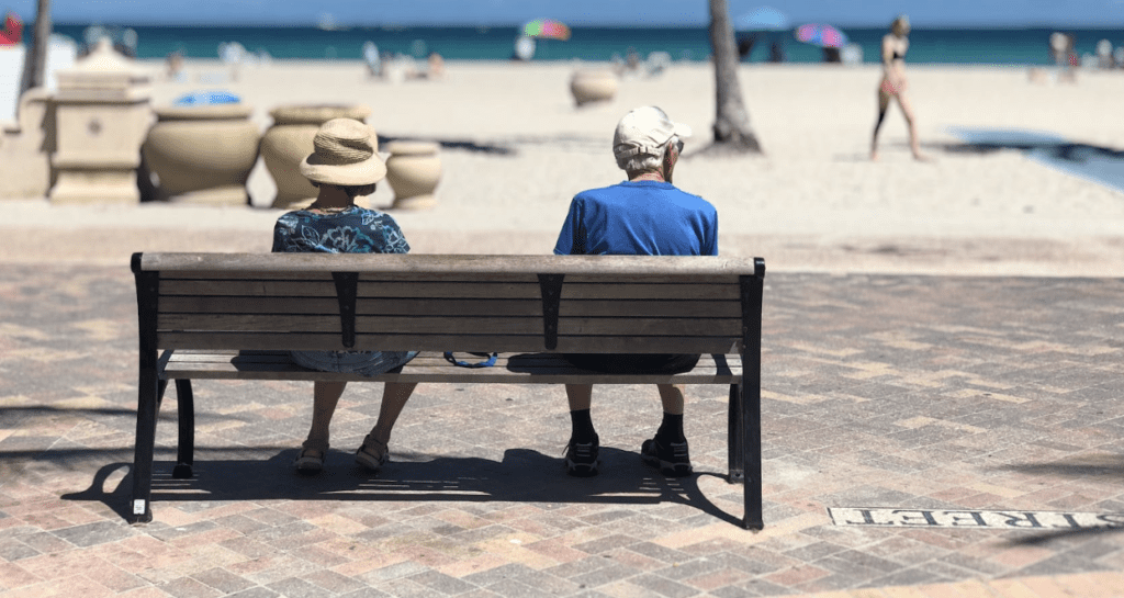 Why Panama is a great place to retire. Pensionado visa retirees on bench beside beach